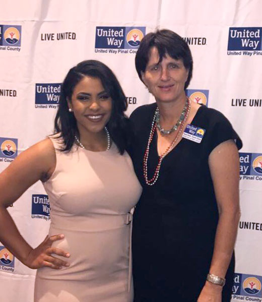 SSVF Project Coordinator Tianna Cann standing with Mannie Bowler, Executive Director of United Way Pinal County in front of a white curtain with United Way logos dotted across its surface.